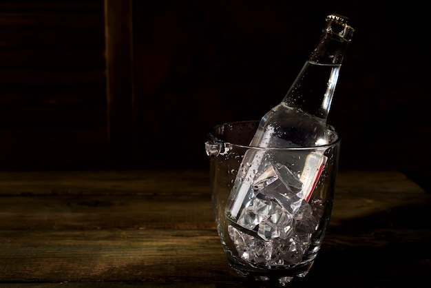 Glass ice bucket with a bottle of tonic, rum or other alcohol on dark wooden backgorund