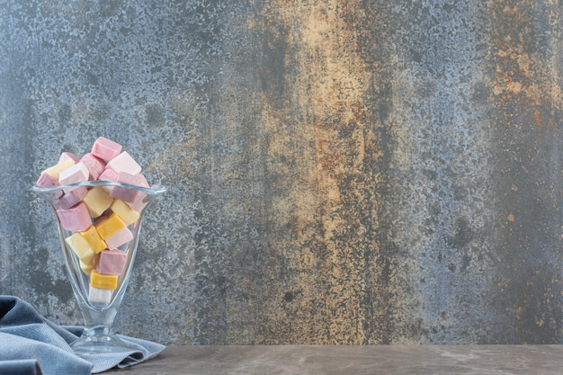 Coppa gelato in vetro piena di caramelle colorate su sfondo grigio.