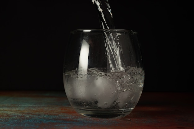 Glass of ice water being filled with cold sparkling water on a dark background and rustic surface.