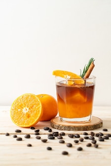 A glass of iced americano black coffee and layer of orange and lemon juice decorated with rosemary and cinnamon on wood background
