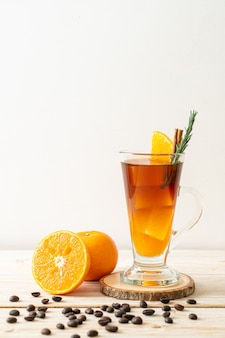 A glass of iced americano black coffee and layer of orange and lemon juice decorated with rosemary and cinnamon on wood surface