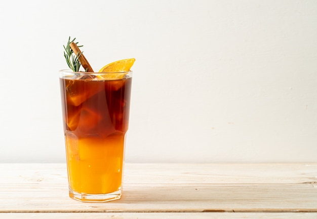 A glass of iced americano black coffee and layer of orange and lemon juice decorated with rosemary and cinnamon on wood table
