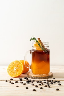 A glass of iced americano black coffee and layer of orange and lemon juice decorated with rosemary and cinnamon on wooden table