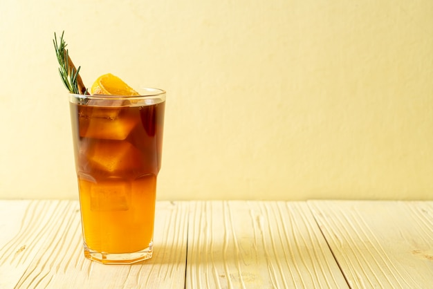 A glass of iced americano black coffee and layer of orange and lemon juice decorated with rosemary and cinnamon