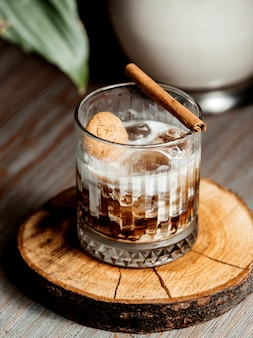 Glass of iced coffee cocktail garnished with cinnamon stick