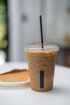 A glass of iced coffee with cheesecake on white table