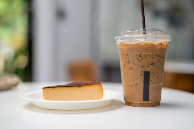 A glass of iced coffee with cheesecake on white table Premium Photo