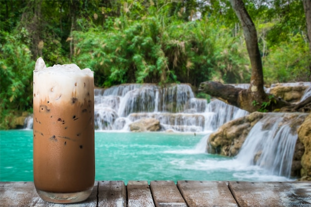 A glass of iced coffee on the wooden table by the waterfall