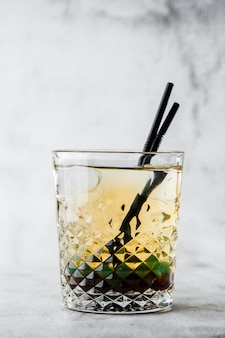 Glass of iced green tea with lemon, isolated on bright marble background. overhead view, copy space. advertising for cafe menu. coffee shop. vertical photo.