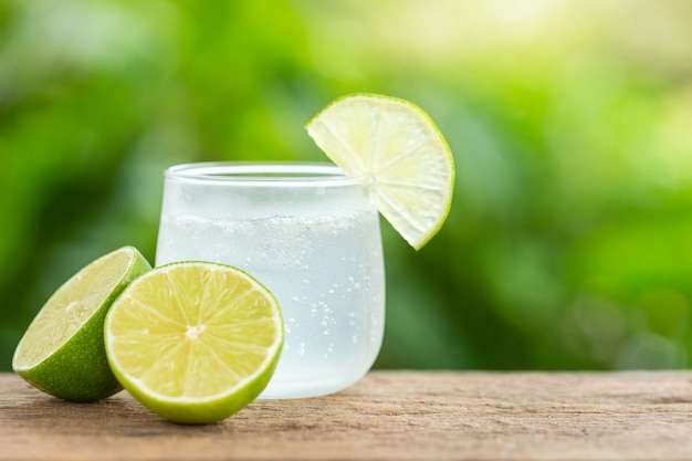Glass of iced lemon soda on wooden table with green blur space for text or design