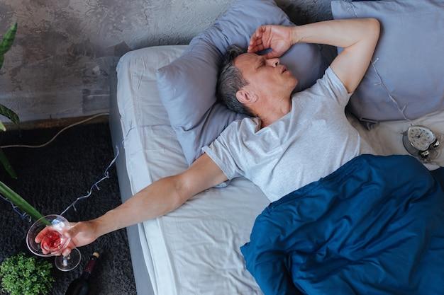 手にガラス。ベッドで休んでガラスを保持している眠そうな成熟した男