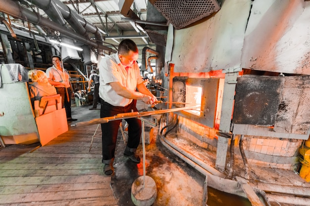 Glass industry workers working with manufacture equipment on production of glass