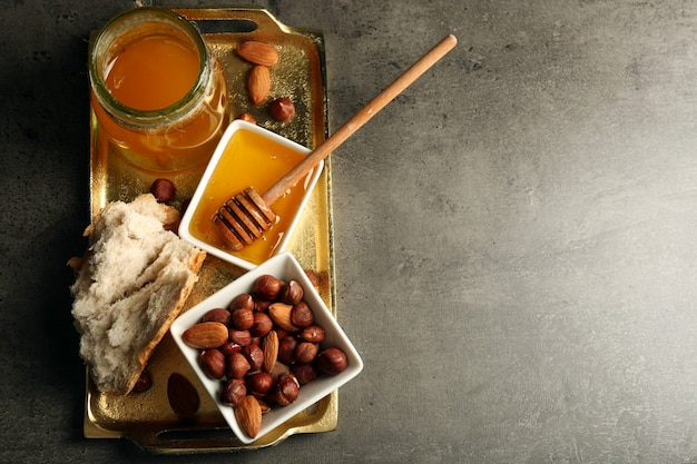 灰色のテーブルに蜂蜜とナッツとガラスの瓶とボウル