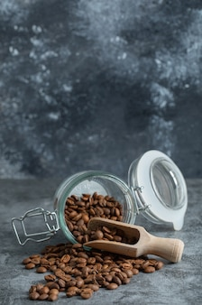 Glass jar of aromatic coffee beans on marble background