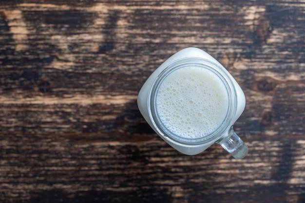 Glass jar of banana milkshake on wooden
