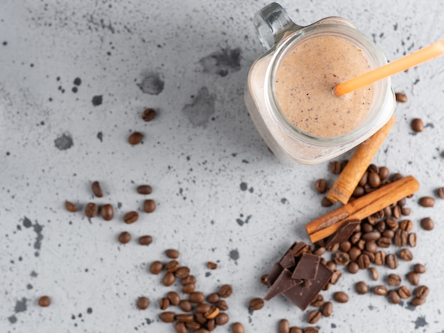Glass jar of chocolate coffee milk smoothie cocktail on grey table