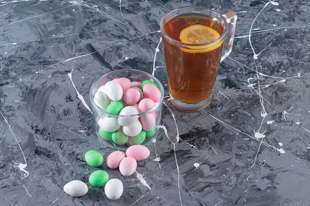 Glass jar of colorful bonbons and cup of black tea on marble table.