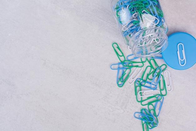 Vaso di vetro di puntine da disegno colorate su superficie bianca.