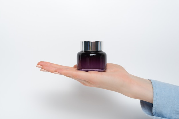 Glass jar for cosmetics in a female hand.