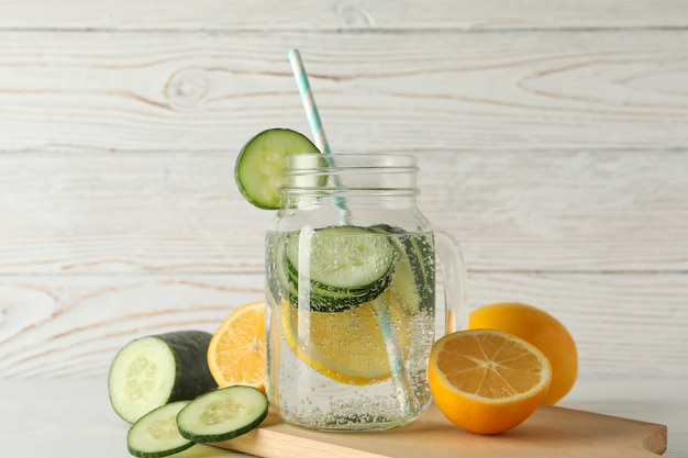 Glass jar of cucumber water, slices and lemons on wooden surface