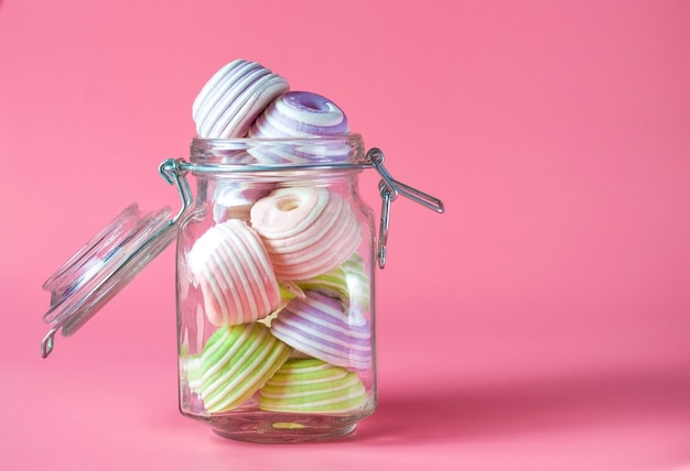 Glass jar filled to the brim with multicolored marshmallows.