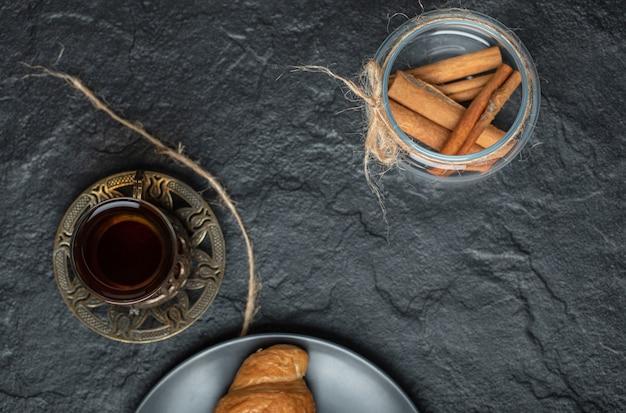 Un barattolo di vetro pieno di bastoncini di cannella con una tazza di tè.