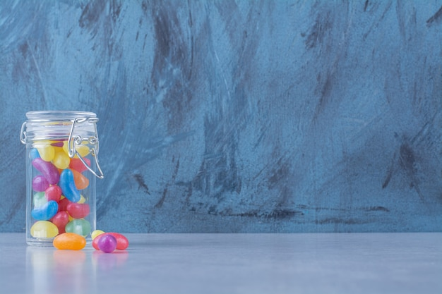 A glass jar full of colorful bean candies .