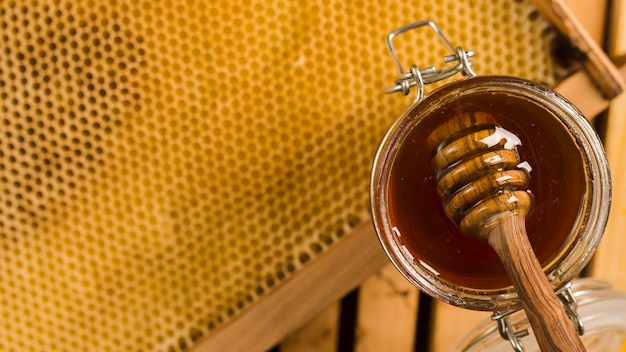 Glass jar full of honey with honey spoon