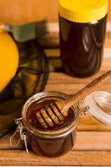 Glass jar full of honey with honey spoon
