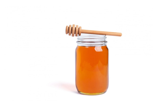 Glass jar full of honey with a wooden dipper on top