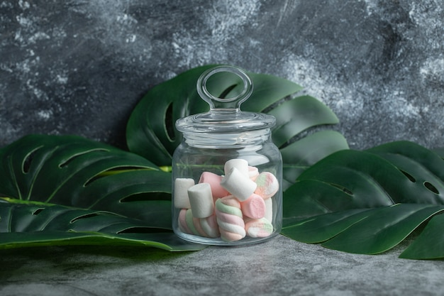 A glass jar full of marshmallows on leaves.