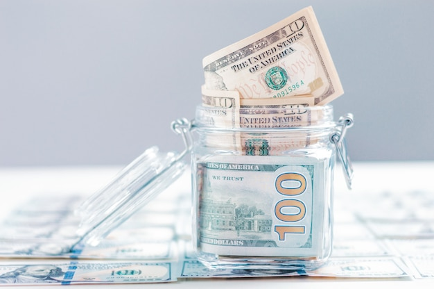 Glass jar full of money. crisis savings concept. mixed media