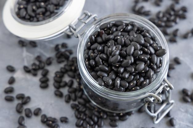 灰色のテーブルのクローズアップに乾燥黒豆でいっぱいのガラス瓶。健康的な食事と菜食主義の概念。伝統的なラテンアメリカのいとこ成分