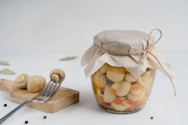ピクルスにしたシャンピニオンマッシュルームでいっぱいのガラス瓶は、木製のテーブルの上にフォークでまな板の上で提供されます