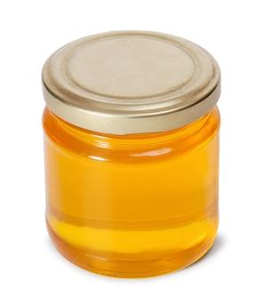 白い背景で隔離の甘い蜂蜜でいっぱいのガラス瓶