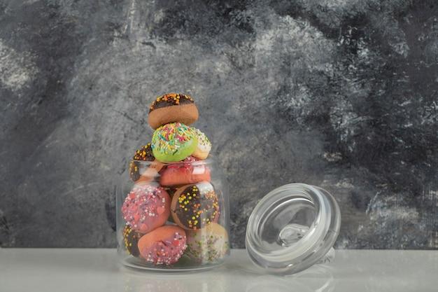 Un barattolo di vetro pieno di piccole ciambelle colorate.
