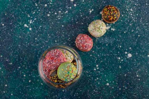 A glass jar full of small colorful doughnuts .