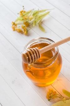 Glass jar of honey, linden flowers
