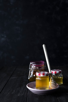 Glass jar of honey and stick on a ceramic plate on a dark concrete background , copy space
