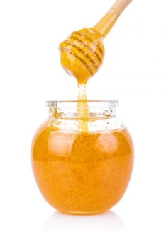 Glass jar of honey and stick isolated on white background