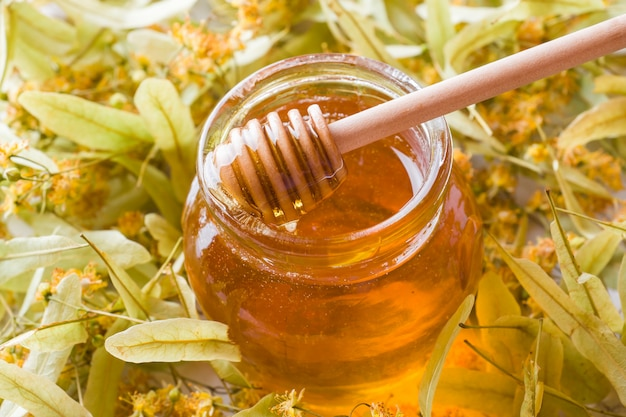 Glass jar of honey on the surface of linden blossoms