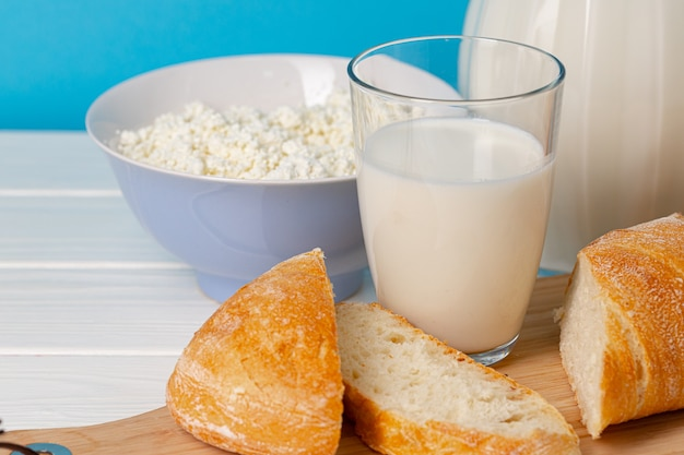 Glass jar of milk, bowl of cottage cheese and bread on wooden table close up