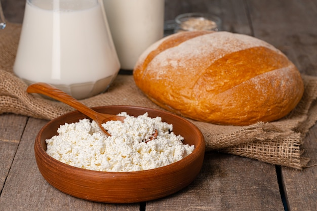 Glass jar of milk, bowl of cottage cheese and bread on wooden table