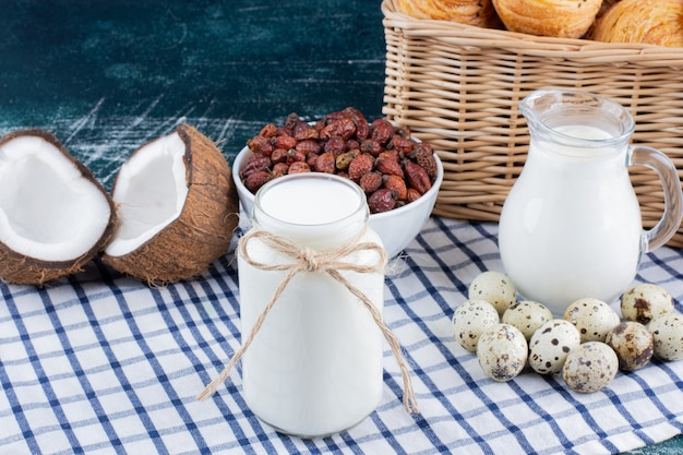 Vaso di vetro di latte, datteri secchi e uova di quaglia sul tavolo di marmo.