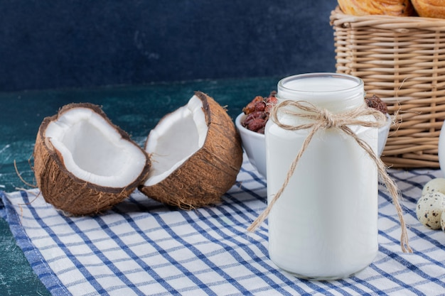 Vaso di vetro di latte e noci di cocco tagliate a metà sul tavolo di marmo.