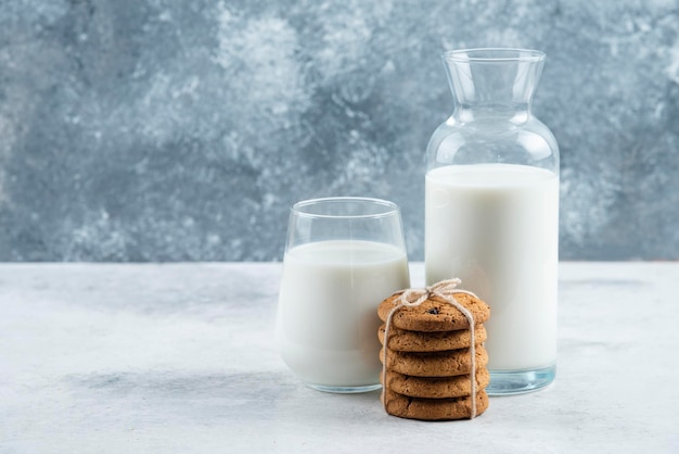 A glass and jar of milk with delicious cookies .