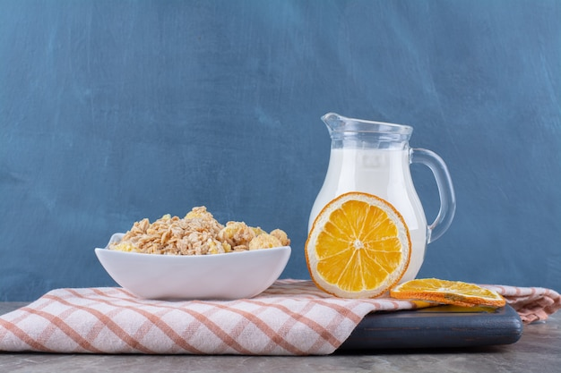 A glass jar of milk with healthy cornflakes and slices of orange fruit on a wooden board.