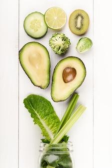緑の健康野菜レタスの葉、ライム、リンゴ、キウイ、アボカド、食品のコンセプトとガラスの瓶のマグカップ。