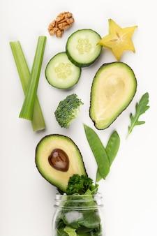 Glass jar mugs with green health vegetables lettuce leaves, lime, apple, kiwi, avocado