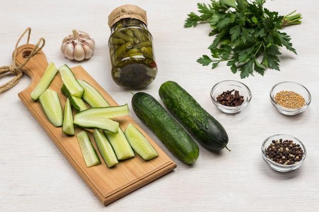 통조림 오이, 신선한 오이, 파슬리, 마늘 및 향신료의 유리 항아리. 수제 발효 제품. 건강한 겨울 음식. 흰색 표면. 평면도.
